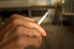 Cigarett i gammal hand Arkivbild