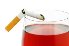 Cigarett med ett exponeringsglas av vin Arkivfoto