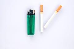 Cigarett och tändare på vit bakgrund Arkivfoto