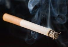 Cigarett på svart bakgrund arkivfoto