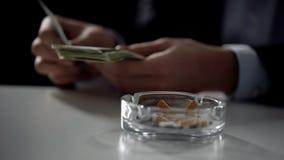 Cigarettaskfat, person som räknar pengar på bakgrund, olagligt affärsavtal fotografering för bildbyråer