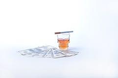 Cigarettdollar och whisky Arkivfoto