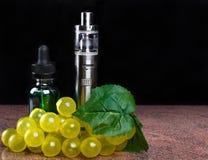 Cigarette électronique, bouteille avec le liquide de vape et groupe de raisins avec la feuille sur le fond noir Photographie stock libre de droits