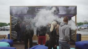 Cigarette électronique de fumée d'hommes sur la rue Festival de Vaper Le football de table de jeu banque de vidéos