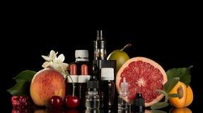 Cigarette électronique, ensemble de liquide pour fumer et fruit frais Images stock