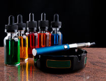 Cigarette électronique sur le cendrier et les bouteilles avec le liquide de vape sur le fond noir Image libre de droits