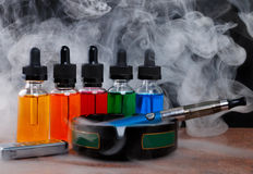 Cigarette électronique sur le cendrier, l'allumeur de cigarette et les bouteilles avec le liquide de vape dans la vapeur sur le f Photographie stock libre de droits