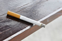 A cigarette. On a wood table Royalty Free Stock Images