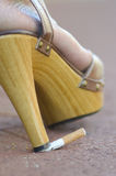 Cigarette abused by high heel shoe Stock Photo