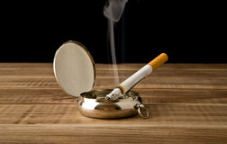 Cigarette in an ash-tray Stock Photos