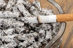 Cigarette ashes in an ashtray and cigarette. Close up Stock Photo