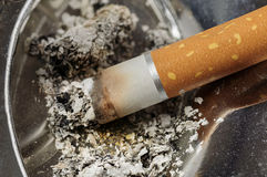 Cigarette and ashes in a metal ashtray Stock Image