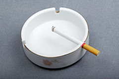 Cigarette on the ashtray. A cigarette lighted is on the ashtray Stock Image