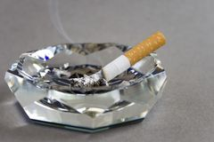 Cigarette and ashtray. Isolated on grey Stock Photos