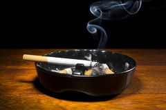 Cigarette in ashtray. A burning cigar in a classic black ashtray streaming smoking in a dark, moody setting.  The smoke is real, straight from the cigarette and Stock Photos