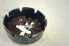 Cigarette in the ashtray on the cement floor. Royalty Free Stock Photos