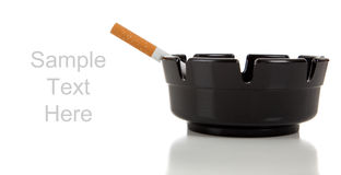 A cigarette in an ashtray on white with copy space Stock Photography