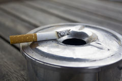 Cigarette and Ashtray on a wood table Royalty Free Stock Images
