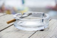Cigarette and ashtray on wooden table Stock Images