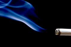 Cigarette avec de la fumée sur le fond noir image libre de droits