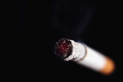 Cigarette on a black background. Cigarette as a symbol of human dependence on addictions stock photo