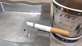 Cigarette brûlant sur le cendrier, tasse de café, tasse égyptienne - fin, détail, macro banque de vidéos