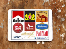 Cigarette brands and logos. Collection of logos and vector of top popular cigarette companies on white tablet on rusty wooden background. brands like marlboro Stock Image
