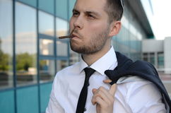 Cigarette break. Young businessman smoking cigarette outside an office Stock Image