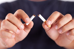 Cigarette broken. In two by man who has a smoking addiction Royalty Free Stock Photography
