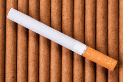 Cigarette with brown filter on dark cigarettes Royalty Free Stock Photos