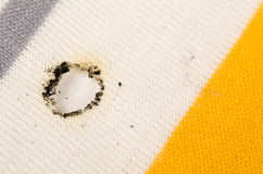 Cigarette burn. In the cotton fabric of a  shirt Royalty Free Stock Images