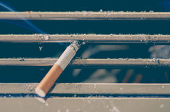 Cigarette burn on dirty metal ashtray Stock Photo