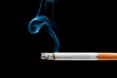 Cigarette burning. A cigarette burning isolated on a black background Stock Image