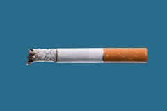 Cigarette burning on blue background Royalty Free Stock Image