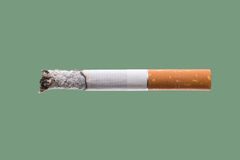 Cigarette burning on green background Royalty Free Stock Image