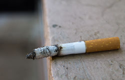 Cigarette burning on a ledge. Close-up of a cigarette left on a ledge, burning with the ash waiting to fall royalty free stock photos
