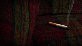 Cigarette Burning Sofa - Fire Hazard Concept. Cigarette left on sofa or chair unattended and burning the fabric stock video