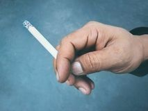 Cigarette burns on dirty hand. Stock Image