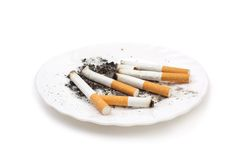 Cigarette buts on plate Royalty Free Stock Photography