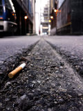 Cigarette butt in alley. Discarded cigarette in urban alley, Chicago Royalty Free Stock Photos