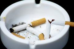 Cigarette butt in ashtray - No smoking. Cigarette butt in ashtray on black - No smoking Stock Photos