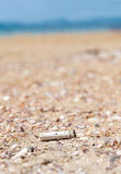 Cigarette butt discarded left on beach, concept photo Stock Photography