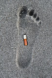 Cigarette butt in a foot trace Stock Images