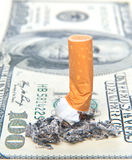 Cigarette butt llaying on money Stock Photography
