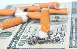 Cigarette butt llaying on money Stock Images