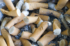 Cigarette butts. An ashtray full of ash and cigarette butts Royalty Free Stock Image