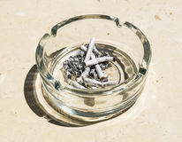 Cigarette butts from ash in the glass ashtray Stock Photos