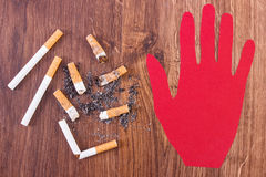 Cigarette butts and ash with hand made of red paper Royalty Free Stock Photography