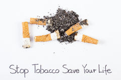 Cigarette butts and ash, stop tobacco save your life Stock Images