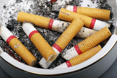Cigarette butts in ashtray Stock Photos
